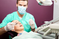 Male dentist examines mouth of woman on the dentist's chair Royalty Free Stock Photo