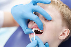 Male dentist examines the teeth of the patient cheerful boy. Royalty Free Stock Photography
