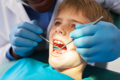 Male dentist examining boy teeth. African male dentist examining little boy teeth close up Royalty Free Stock Images