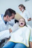 Male dentist examining girls teeth Royalty Free Stock Photo