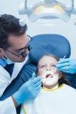 Male dentist examining girls teeth Royalty Free Stock Photography