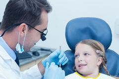Male dentist examining girls teeth Stock Photos