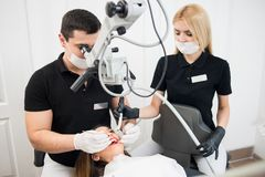 Male dentist and female assistant treating patient teeth with dental tools at dental clinic office. Male dentist and female assistant treating patient teeth with Stock Photos
