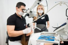 Male dentist and female assistant treating patient teeth with microscope at dental clinic office. Dental equipment. Male dentist and female assistant treating Stock Photos