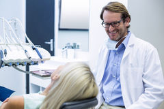 Male dentist interacting with female patient. In dental clinic Royalty Free Stock Photography