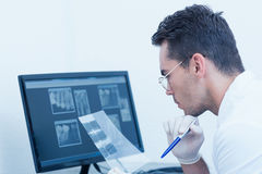 Male dentist looking at x-ray. Concentrated male dentist looking at x-ray Royalty Free Stock Photography
