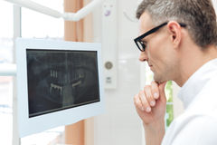 Male dentist looking teeth on digital X-Ray computer monitor royalty free stock images