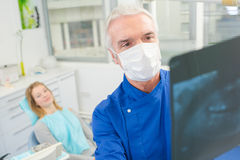 Male dentist looking at xray Royalty Free Stock Images