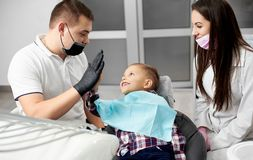 Male dentist and lovely kid after treating teeth giving high-five. Male dentist and his assistant with lovely kid after treating teeth at dental clinic office Royalty Free Stock Image