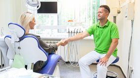 Male dentist shaking hands with satisfied patient. Male dentist shaking hands with satisfied smiling patient Royalty Free Stock Images