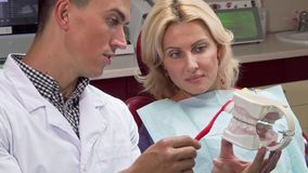Male dentist showing his patient how to brush teeth on a jaw mold. Cropped shot of a dentist talking to his mature female patient during medical appointment stock photos