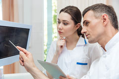 Male dentist showing something on the computer monitor. To female nurse at clinic royalty free stock photos