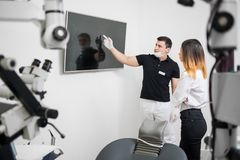 Male dentist showing to female patient her dental x-ray image on computer monitor in a dental clinic Royalty Free Stock Photo