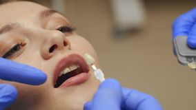 Male dentist treating teeth to young woman patient in clinic. Dental check up stock footage