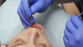 Male dentist treating teeth to young woman patient in clinic. Dental check up stock video