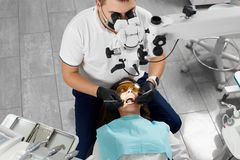 Male dentist treats female patient using microscope use new technologies. Male dentist with an assistant in a black mask and gloves treats a patient using a Royalty Free Stock Photos
