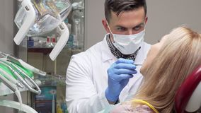 Male dentist wearing medical mask examining teeth of female patient. Cropped shot of a professional dentist working at his clinic, checking teeth of a woman royalty free stock image
