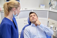 Male dentist with woman patient at clinic Stock Photo