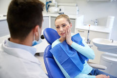 Male dentist with woman patient at clinic Stock Images