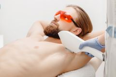 Male depilation laser hair removal procedure treatment in salon. Male depilation laser hair removal underarms procedure treatment in salon. Health and beauty stock photos