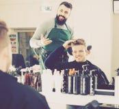 Male describing his desirable haircut. To hairdresser at hair salon Stock Photography
