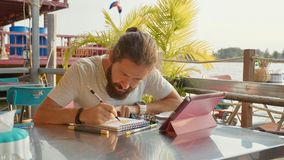 Male designer draw sketches in open air riverside cafe. Male bearded designer draw sketches in open air riverside cafe and using the tablet Stock Photos