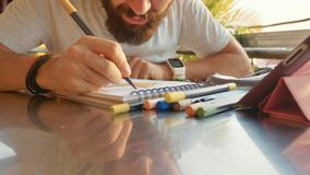 Male designer draw sketches in open air riverside cafe. Male bearded designer draw sketches in open air riverside cafe and using the tablet, close-up Stock Photography