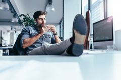Young man drinking coffee during break in office Stock Photos