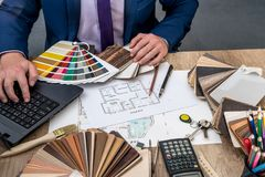 Male designer at office with wooden color swatches. House project Stock Image