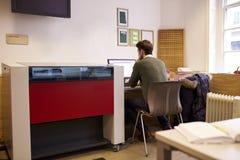 Male Designer Operating CAD System For Laser Cutter Stock Image