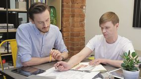 Male designer talks about blueprint to colleague, sitting in office. Young man holds palette and points to paper documentation with pen, telling in detail stock footage
