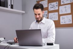 Male Designer Using Laptop. Happy Young Male Designer Using Laptop In Office Royalty Free Stock Images