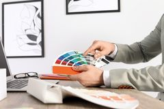 Male designer working with color palette at office table. Closeup royalty free stock image