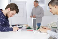 Male designers working on laptop computer at class Royalty Free Stock Image