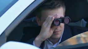 Male detective looking through binoculars sitting car, journalist investigation. Stock footage stock footage
