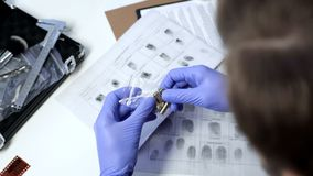 Male detective wearing gloves examining bullets from crime scene in office. Stock photo stock images
