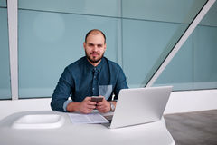 Male developer posing with mobile phone after working on net-book while sitting in modern interior, Stock Images