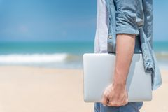 Male digital nomad hand holding laptop on the beach. Male hand holding laptop on the beach, working outdoor in summer season, digital nomad man lifestyle Royalty Free Stock Photography