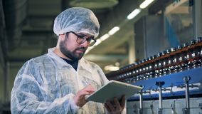 Male distillery specialist in glasses is standing and working with a computer. 4K stock footage