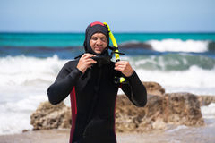 Male diver with diving suit snorkel mask fins on the beach. In Summer Royalty Free Stock Images
