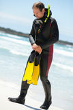 Male diver with diving suit snorkel mask fins on the beach. In Summer Stock Image