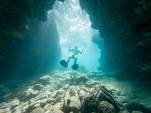 Male diver swimming through natural underwater tunnel. Exploring the coastline royalty free stock images