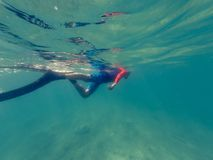 Male diver swimming in ocean enjoying summer. Snorkling in blue water Stock Image