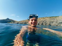 Male diver swims in a mask taking a selfie on the surface. Of the water in nature Royalty Free Stock Images