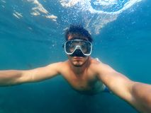 Male diver swims in the sea under the blue water with a mask. And snorkel is taking a selfie Stock Photo