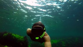 Male dives with shooter camera in hand. Young Diver Underwater Shot Wildlife, the man in the mask and snorkel dives under the water, he swims along the reef stock footage