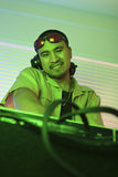 Male DJ with hands on turntable. Asian young adult male DJ behind mixing equipment looking at viewer smiling Stock Photos