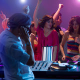 Male dj mixing music at party with dancing people Royalty Free Stock Image