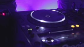 Male DJ's hands playing music on sound board, people dancing, enjoying nightlife. Stock footage stock video