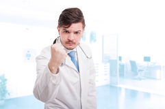 Male doctor acting aggressive and showing his fist. And threatening someone with copyspace Royalty Free Stock Images
